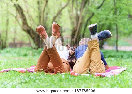 Young Attractive European Couple With Small Dog Beetwin Them Is Getting Rest On Blanket In Some Summ