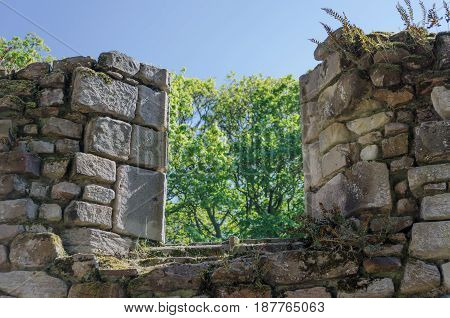 A partially collapsed window in an old stone monastery