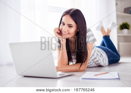 Cute Teen Is Doing Her University Project At Home On The Floor Using Her Laptop. She Is Excited And