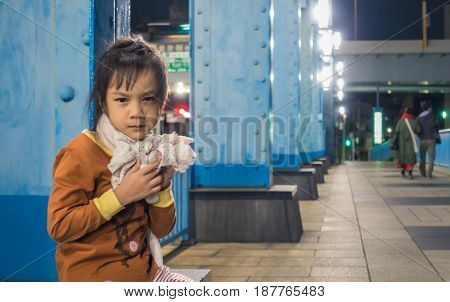 Lonely and sad girl with parent walk away in the background.