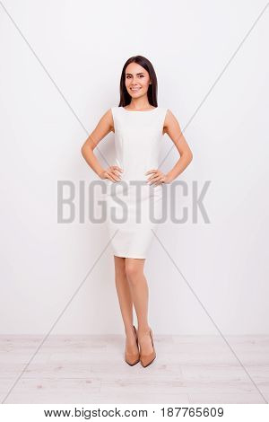 Full Size Portrait Of Beautiful Model In Nice White Dress. She Is In Light Room. Her Hands Are On Hi