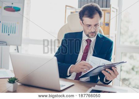 Mature Business Man Is Reading His Notes, Preparing For The Meeting. He Is Broker, Wearing Suit And