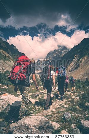 Group of hikers with backpacks climb to the peak of mountain. Caucasian mountains Georgia Svaneti region. Instagram stylisation.