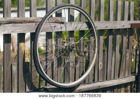 Bicycle wheel. Old bicycle tyre on wooden fence.