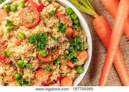 A closeup of a vegetable couscous with parsley, cherry tomatoes, and green peas, with fresh carrots