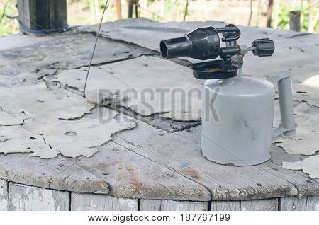 Blowtorch on wooden table background. Propane blowlamp.