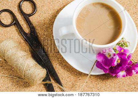 Flowers scissors and jute next to cup of coffee on cork board.