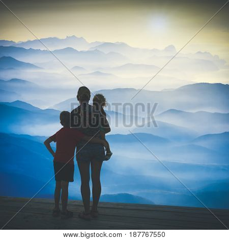 Silhouette of family watching sunrise above the misty mountain valley. Instagram stylisation.
