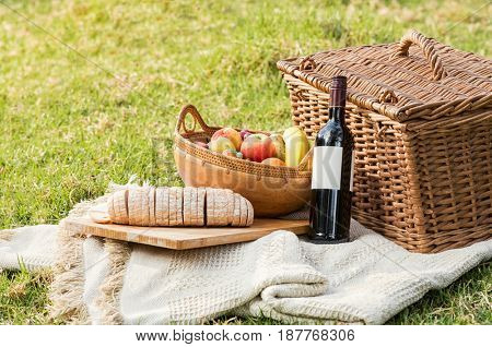 Picnic basket with bottle of wine, fruit and bread on tablecloth. Close up of food and drinks during picnic in a summer day. Red wine with picnic basket and healthy food on white blanket.