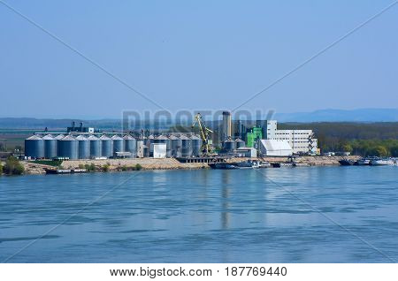 River port with ships, silos, lifting cranes, tanks, warehouses and industrial buildings