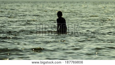 Sihouette of boy playing in the ocean in the late afternoon