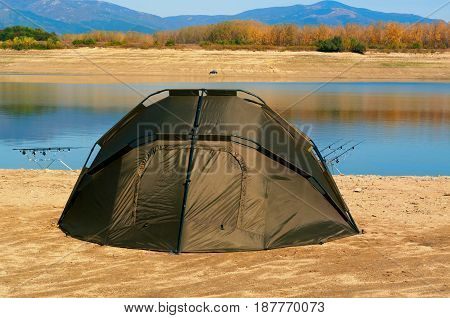 Fishing rods with reels on a support system (rod pod) and tourist tent the holiday camp on the bank.