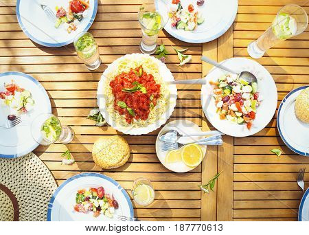 Family dinner variety of Italian dishes on wooden table in the garden top veiw
