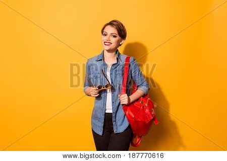 Portrait Of Pretty Young Smiling Female Student Dressed In Jeans Shirt With Sunglasses In Hand And R