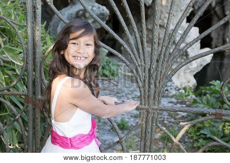 Beautiful Girl With Long Hair In Front Of The Park Gate