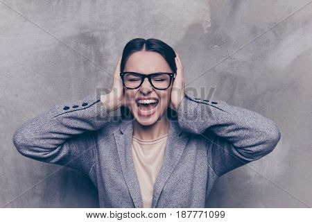 Close Up Of A Stressed Brunette Woman Yelling With Closed Eyes And Ears
