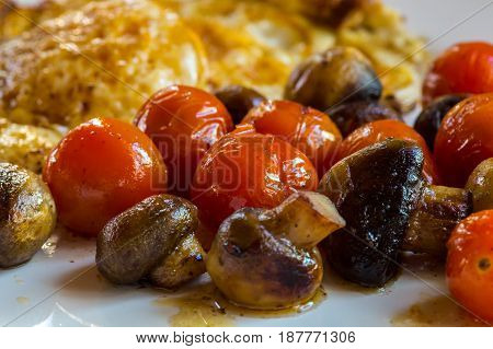 Muschrooms Tomatoes And Egg On A White Plate