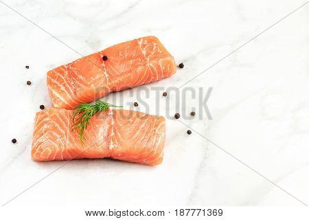 A photo of two slices of salmon on a white marble table with a place for text, with salt, pepper, and dill sprigs