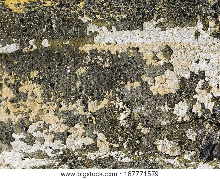 Worn concrete texture with flecked white yellow and orange paint