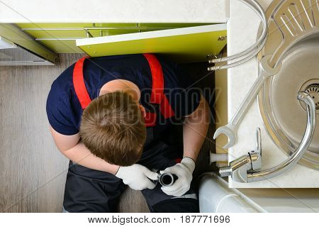 Plumber In The Kitchen Repairing The Water Pipe: Top View