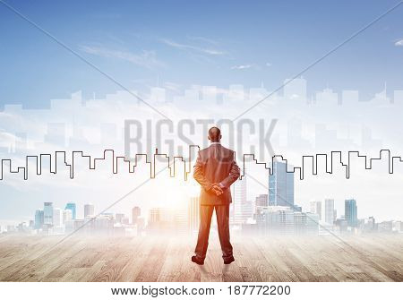 Businessman standing with back and looking at silhouette of modern business center