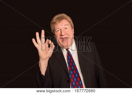 The happy senior businessman showing sign OK and laughing on black studio background. Concept of success in business