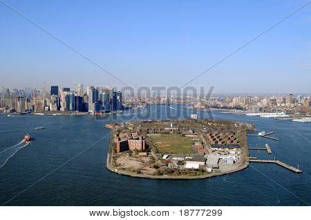 Governors Island in the New York City harbor on a clear spring day. Downtown Manhattan to the left, East River in the back center, and Brooklyn to the right.