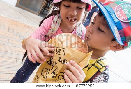Tokyo Japan - May 1 2017: Asian Kids is eating Asakusa's Famous Melonpan bread.