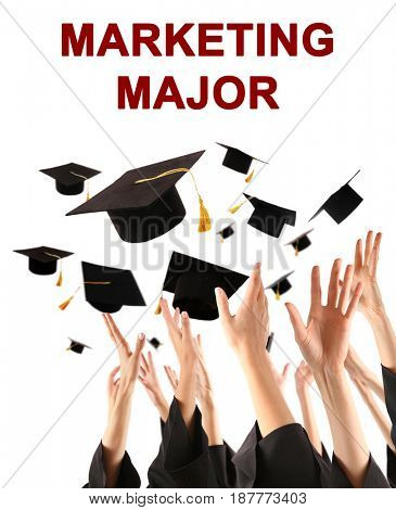 Marketing major concept. Students throwing graduation caps against white background