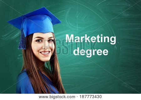 Marketing degree concept. Woman in graduation gown and cap on chalkboard background