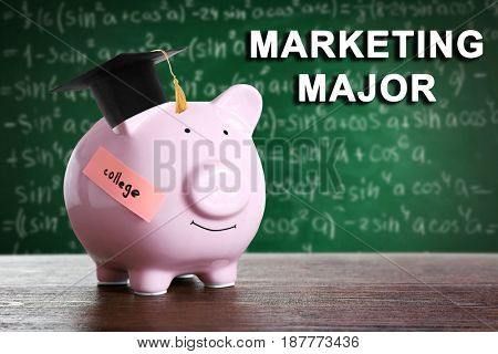 Marketing major concept. Piggy bank in graduation cap on blackboard background