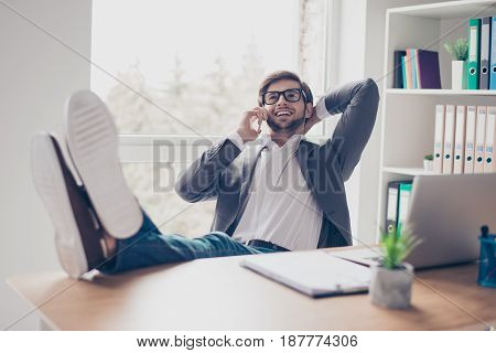 Cheerful Young Successful Man Is Talking On The Phone At The Workplace With Feet On The Table. He Is