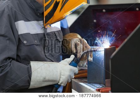 Welder. Worker with protective mask welding metal.