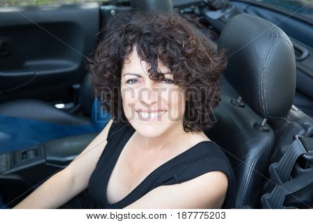 Middle-aged Woman Sitting In A Convertible Car