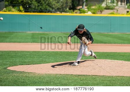 Mens' baseball pitcher throwing the curveball with maximum spin.