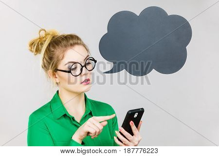 Focused business woman wearing green shirt and red eyeglasses looking at phone with black thinking or speech bubble next to her.