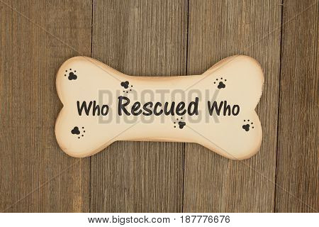 Rescuing a dog A wood dog bone on a weathered wood background with text who rescued who