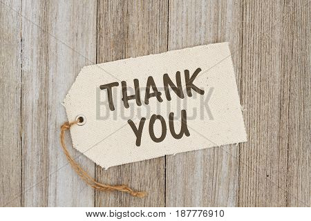Thank you for the gift A cloth gift tag on weathered wood with text Thank You
