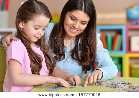 Mom and daughter having fun together at the table