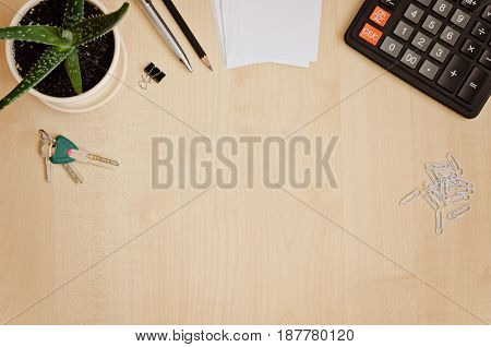 Top view office desk with paper for notes calculator indoor plant and keys. Copy-space composition