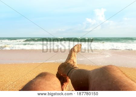 A man is relaxing on the sandy beach of the Indian Ocean. Marine background.