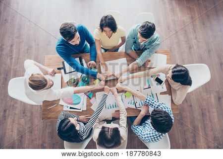 Top Up Of Colleagues Putting Their Fists Together In Round On Top Of The Table With Work Stuff In Th