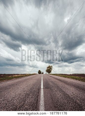 Conceptual photography of asphalt road between the fields and a beautiful dramatic sky