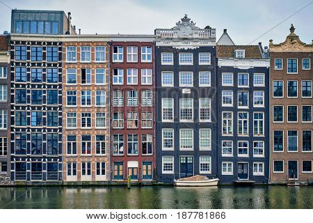 Row of typical houses and boat on Amsterdam canal Damrak with reflection. Amsterdam, Netherlands