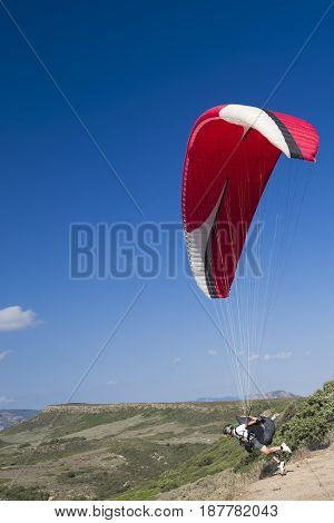 Colorful hang glider in sky over green mountain in Sardinia
