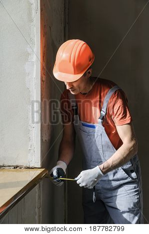 Worker is checking the correctness of the installation of a window sill. He is measuring the distance from the wall to the edge of the sill.