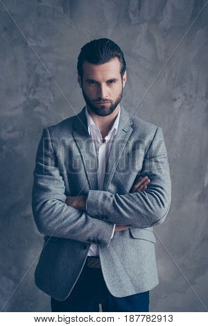 Success Concept. Stylish Young Bearded Man Is Standing On Pure Gray Background. He Looks So Classy!