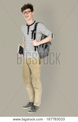 Caucasian young man standing with backpack and tablet