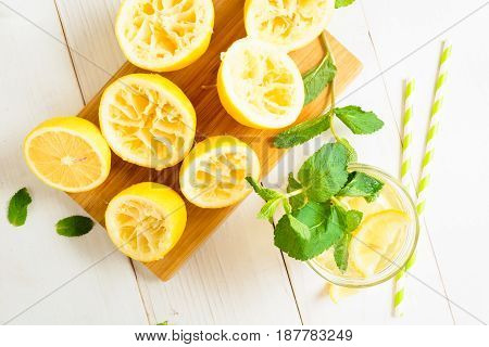 Lemonade With Mint And Squeezed Lemons On Board With Straw