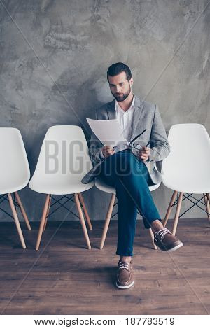 Serious Confident Bearded Young Man In Formal Wear Is Preparing For An Interview, Sitting In The Hal